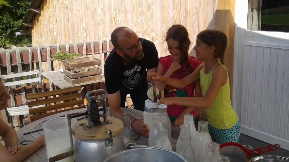un homme et deux filles faisant du beurre